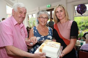 Cutting the 20th anniversary cake are Jeff Shaw, tenant at Pound Green Court, Marlene Smyth, scheme co-ordinator and Carol Ervine, group director of tenant & client services at Choice Housing.