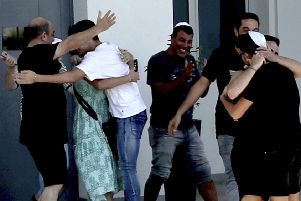An Israeli teenager is embraced by relatives after being released by police in Paralimni, Cyprus, Sunday, July 28, 2019. He was one of seven Israeli teenagers who were detained as suspects in the alleged rape of a 19-year-old British woman. She was arrested and faced a public nuisance charge. (AP Photo/Petros Karadjias)