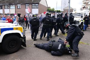 A P.S.N.I. officer is dragged to safety after he is struck on the head during disturbances in New Lodge on Thursday. (Photo: Pacemaker)