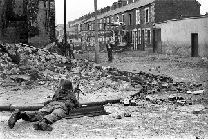 A British Army soldier on lookout in the Falls Road area of Belfast.