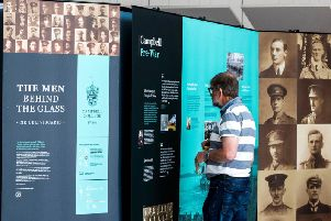 An Old Campbellian reads details about former pupils of Campbell College Belfast who fought in WW1 at the opening of The Men Behind The Glass exhibition at the Public Record Office of Northern Ireland (PRONI).