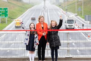 DfI Permanent Secretary Katrina Godfrey cuts the ribbon assisted by two local primary school pupils