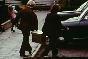 Footage from a lost documentary of two men carrying a bomb used in an attack on the Queen's University Sports Hall in Belfast