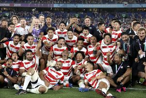 Japan players and management celebrate after defeating Scotland 28-21. (AP Photo/Christophe Ena)
