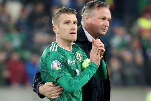 Michael O'Neill - in an embrace with captain Steven Davis - heads off the pitch on Saturday following what is expected to prove his final home game as Northern Ireland manager. Pic by PressEye Ltd.