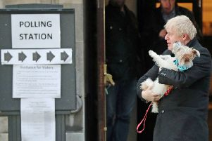 Prime Minister Boris Johnson holds his dog, Dilyn, after casting his vote in the 2019 General Election at Methodist Central Hall, London.