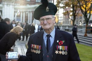 Rowland Todd at the Cenotaph in Belfast with a picture of himself and his brothers who all served in the Second World War