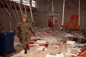 A soldier walks through the aftermath of a bomb attack against an RUC station in Craigavon in December 1991, which also wrecked St Anthony's Primary School
