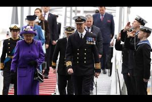 Philip Crozier (far right, middle) pipes Her Majesty The Queen aboard her namesake vessel during the ceremony.