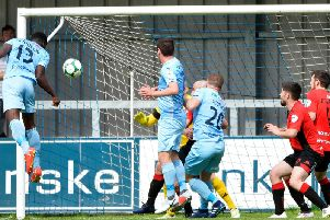Maxim Kouogun heads home the opening goal between Warrenpoint Town and Crusaders.