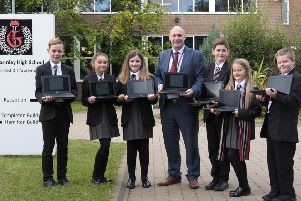 Mr Massey and pupils showcase some of the new computers.
