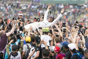 Lewis Hamilton crowdsurfs after his fourth consecutive British GP win