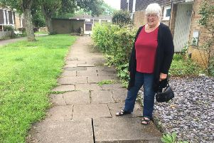 Dianne Finnie next to the uneven paving slabs between Tonmead Road and Mounts Court