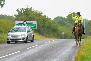 A Northamptonshire Police volunteers on horseback rider waves past a more considerate driver during the Operation Close Pass test