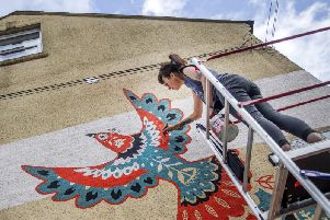 Amy pictured finishing off the folk art-style bird from her ladders this morning (Tuesday). Pictures by Kirsty Edmonds.