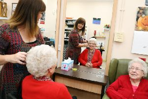Hairdresser Gillian Lamb puts the finishing touches to Margaret Sykes, watched by Tess Porter.