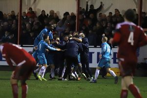 Tom Knowles is mobbed by his Kettering Town team-mates after his late free-kick sealed a 2-1 victory at Stourbridge and sent the Poppies to the top of the league. Picture by Peter Short