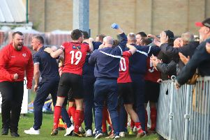 Aaron O'Connor is mobbed by players, staff and fans alike after his last-gasp goal gave Kettering Town a 1-0 win at Leiston and put them on the brink of the title. Pictures by Peter Short