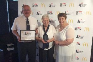 David (Left) and Hazel (centre) Burgess collect the Northants FA 'Grassroots League of the Year' award.