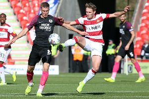 Josh Knight of Peterborough United battles for the ball with Kieran Sadlier of Doncaster Rovers. Photo: Joe Dent/theposh.com./