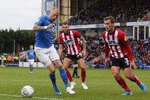 Marcus Maddison of Peterborough United takes on Harry Toffolo and Jorge Grant of Lincoln City. Photo: Joe Dent/theposh.com