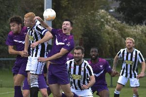 Peterborough Northern Star's Herbie Panting (stripes) challenges for a header in the match against Loughborough University. Photo: Brian Colbert.
