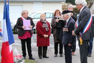Veteran John Jenkins  lays a wreath with local mayor Alain Scribe, far right, at Pioneers Street,  Asnelles, close to where he landed in 1944