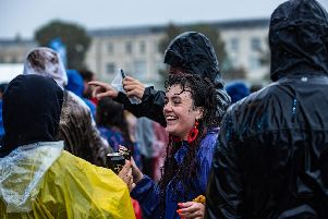 Pouring rain doesn't stop fans at the Common Stage smiling. Picture: Vernon Nash