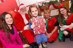 Sophie Vaughan-Smith, four, visits Santa in his grotto. pictured with mum Fiona Vaughan-Smith, left, and elves  Sue Westwood and Holly Curtis, right,'Picture: Duncan Shepherd