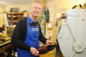Clive Barrett, 62, owner of Barrett's Shoe Reapair Shop, polishing a pair of repaired shoes. Picture: Sarah Standing (220319-2796)