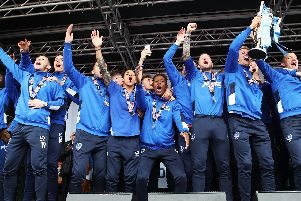 Michael Doyle lifts the League Two trophy as Pompey celebrate the title win. Picture: Joe Pepler