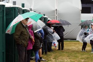 People shelter from the wind and rain behind the loos.       'Picture: Chris Moorhouse