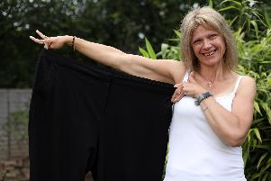 Trixi Ellis has lost 10 stone. She is pictured at home in Havant with a pair of trousers that used to be 'a bit tight'.               Picture: Chris Moorhouse          (120619-18)