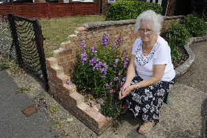 Edna Bennett surveys the damage to her garden wall in Leigh Park after it was hit by a delivery driver. Picture: Ian Hargreaves  (100719-1)