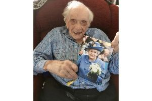 Reginald Tegg with a card from the Queen on his 100th birthday