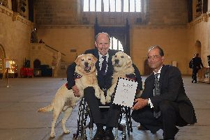 Allen Parton receiving his Points of Light award from his local MP Sir George Hollingbery, accompanied by his two assistance dogs EJ (Endal Junior) and Rookie