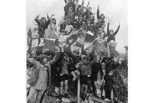 Children stage their bonfire sit-on to stop any move by the council to move it