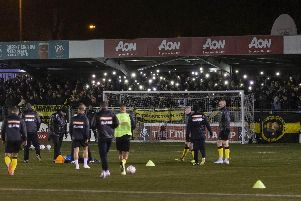 Harrogate Town fans hold their phones up as torches as the power goes out at Wetherby Road  Picture: Daniel Chesterton
