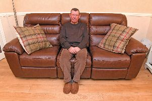 Graham Freake with the Oak Furnitureland leather settee 'Picture: Malcolm Wells (301019-9255)