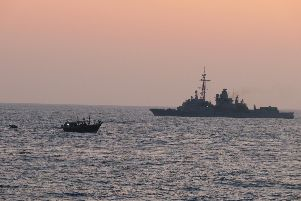HMS Montrose pictured next to the dhow as a Royal Navy boarding party approaches. Photo: MoD/Chris Daly
