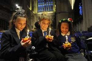 The News annual Christingle service, attended by schools from throughout the city, has been held in front of a packed congregation at St Marys Church in Fratton. Arundel Court Primary Academy pupils, from left, Libbie Hayes (10), Dennis Jelly (10), and Daniella Uzoamaka (eight).'Picture Ian Hargreaves  (181209-1_chistingle)