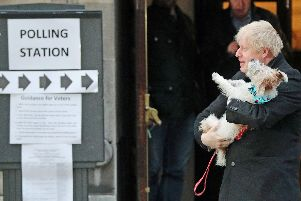 Prime Minister Boris Johnson holds his dog, Dilyn, after casting his vote in the 2019 General Election at Methodist Central Hall, London. Picture: Jonathan Brady/PA Wire