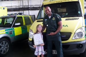 Eight-year-old Maia Bryant with paramedic Phil Ibrahim and her award after helping save her great-grandfather. Photo by SECAmb SUS-161208-102500001