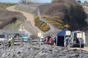 Police have closed off the beach while investigations continue. Photo by Eddie Mitchell. SUS-180504-130426001