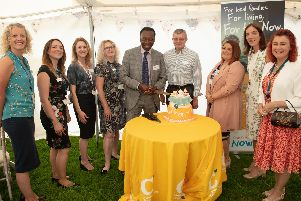 Patron Ambrose Harcourt cutting the birthday cake at the party for Chestnut Tree House