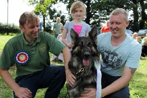 Richard Morris, from Fenwold Vets, left, awards Gary and Bethany Hughes' dog Taz with first place in the fun dog show.
