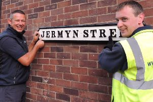 Window cleaners Paul Dunham and Matt Gillard putting back one of the refurbished cast iron street names in Sleaford. EMN-180928-092808001