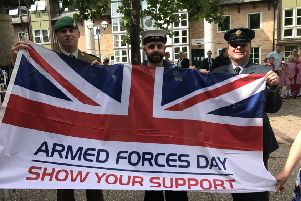Forces personnel with the Armed Forces Day flag in Sleaford. EMN-190419-113240001