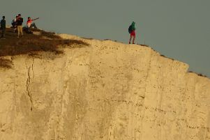 Youth urinating off the cliffs at Seven Sisters. Photo by Wayne Spring / SWNS SUS-180927-110457001