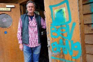 Bobby Schuck next to the Bev Gang graffiti tag left after the break-in. Photo by Steve Robards